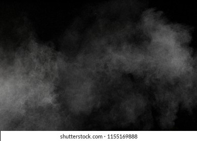 Abstract white powder explosion. White dust debris isolated on black background.