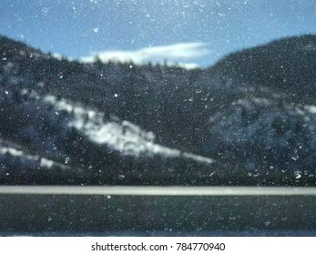 Abstract winter destination concept image. Perspective of passenger inside of a car or auto looking through the car window, dirty with road way salt, at the beautiful snowy mountain scenery