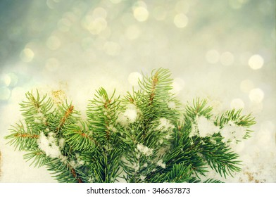 Abstract winter festive background for Christmas and new year for your design. A Christmas card with a fir tree branch on a snow background with bokeh