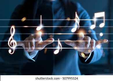 Abstract woman hands playing music notes on dark background, music concept