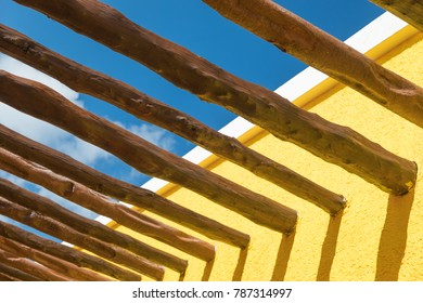 Abstract Wood Post Beams and Bright Yellow Wall Against Blue Sky