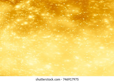 Abstract xmas Golden sparkles or glitter lights. Christmas festive gold background. Defocused bokeh  particles. Template for design