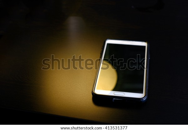 Abstract yellow light with smart phone on the table ,dark style