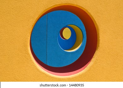 Abstract yellow wall with hole to view blue wall, which also has a hole to view a red wall
