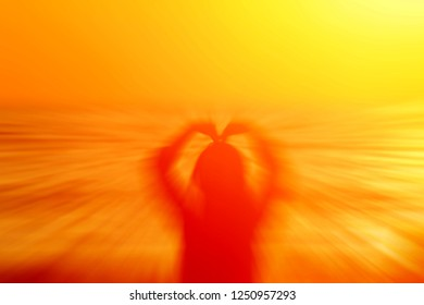 An abstract of a zoom in human figure forming a love shape using hands above head during golden sunset.