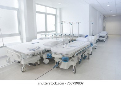 Abstracted perspective background of empty stretcher gurney beds at the corridor emergency ward in modern hospital
