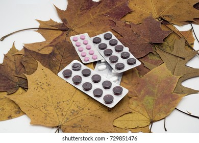 Abstraction of an autumnal cold. Pills on yellow maple leaves.