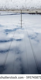 Abstraction of high-voltage wires in a winter snow-covered field against a background of blue clear sky