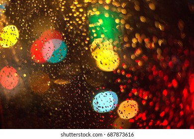 Abstraction out of focus. Drops of rain on the glass. Lights of the night city. Background blur