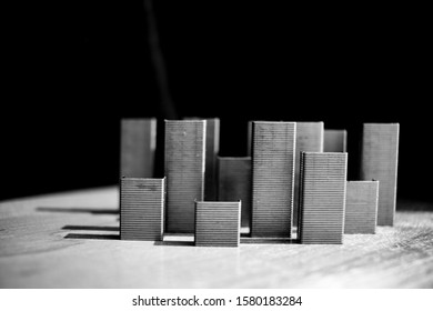 Abstraction A simulated city created from staples forming skyscrapers with a dark background and shadow.