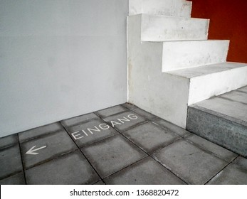 """Abstrakt view onto a Corner of a Building with Stairs an lable """"Entrance"""" on the Floor"""