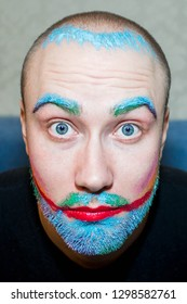absurd male make-up of a bald gay with a beard for Halloween, which the girl drew with pastel crayons for hair