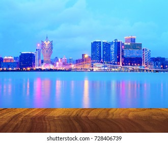 Abtract Macao,Macau city in dusk in background with wooden table in foreground.