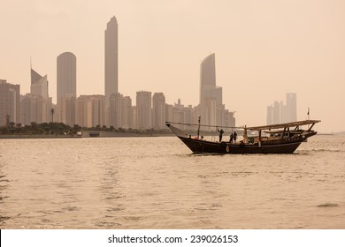 Abu Dhabi buildings skyline with old fishing boat on the front.