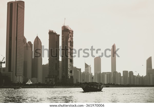 Abu Dhabi buildings skyline with old fishing boat on the front
