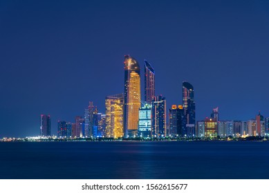 Abu Dhabi downtown night skyline reflected in the seaside, capital city of the UAE