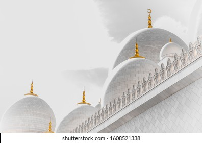 Abu Dhabi grand mosque in white with the golden howl moon on the dome and a white background, creative abstract photography