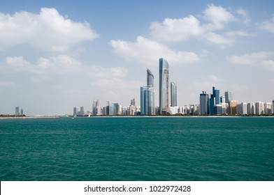 Abu Dhabi skyline and the beach at forefront.