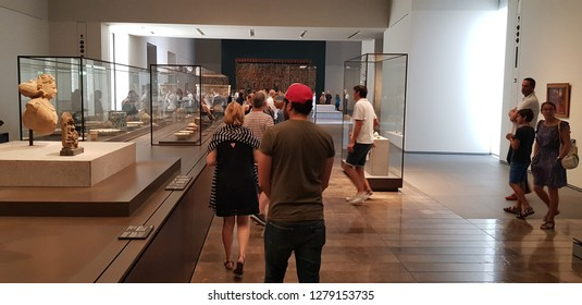 Abu Dhabi, UAE - 2018 - Tourists and Visitors viewing and admiring antiques at in the new art and civilization museum Louvre Museum in Abudhabi, United Arab Emirates