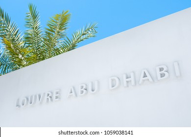 Abu Dhabi, UAE - 27 March 2018: The name of the museum on the white wall in Louvre Abu Dhabi main entrance, Saadiyat island