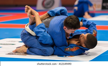 ABU DHABI, UAE - APRIL 19, 2016: ABU DHABI WORLD PROFESSIONAL JIU-JITSU CHAMPIONSHIP 2016 in the IPIC ARENA. Fighters in blue kimono on the mat.
