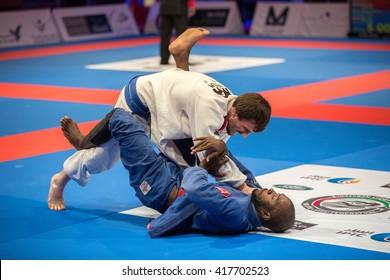 ABU DHABI, UAE - APRIL 19, 2016: ABU DHABI WORLD PROFESSIONAL JIU-JITSU CHAMPIONSHIP 2016 in the IPIC ARENA. Fighters in the white and blue kimonos fight in parterre.