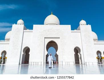 ABU DHABI, UAE - APRIL, 2016: Local arab man in white kandura walking in the courtyard of beautiful Sheikh Zayed Grand Mosque.