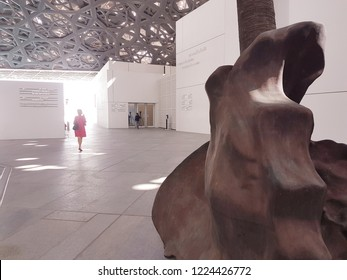 Abu Dhabi, UAE- Circa 2018. Part of sculpture and lady in red dress at background at the Louvre Abu Dhabi