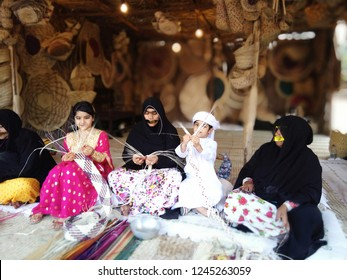 Abu Dhabi, UAE - Circa 2018. Boy and girl make crafts under supervision of two old ladies. all in ethnic dresses
