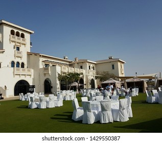 Abu Dhabi, UAE - Circa 2019. Grass terrace with ready for party tables on the sea side of Yas Links Golf club