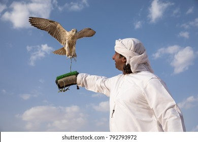 Abu Dhabi, UAE - Dec 15, 2017: Man in a traditional emirati dress proudly posing with his trained show falcon.