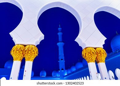 ABU DHABI, UAE - JAN 22, 2019: Sheikh Zayed Mosque or the grand Mosque during evening with white arcs against the blue sky and a minaret.