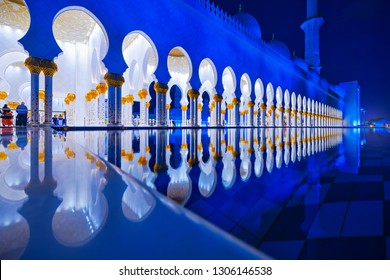 ABU DHABI, UAE - JAN 22, 2019: Sheikh Zayed Mosque or the grand Mosque during evening with a row of white arcs mirrored in the outside pond.