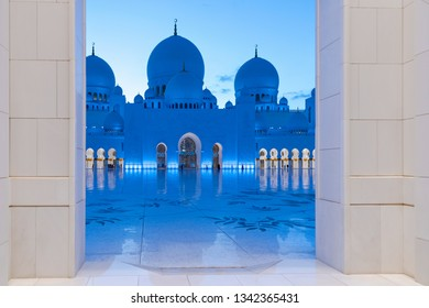 ABU DHABI, UAE - JAN 22, 2019: Framed view into the courtyard at the Sheikh Zayed Mosque or the grand Mosque illuminated during evening.