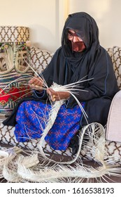ABU DHABI, UAE - JANUARY 12, 2019: Emirati woman wearing burka and traditional dress weaving baskets from dry palm leaves during Zayed Heritage Festival