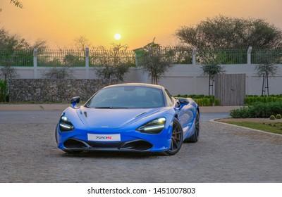 Abu Dhabi / UAE - January 29, 2019: Blue McLaren 720S car in Al jurf Abu Dhabi farm during sunrise