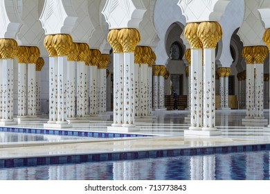 ABU DHABI, UAE. JANUARY 4, 2016: Close-up decorated marble columns on the top with like golden palm with reflected pool in front of Sheikh Zayed Grand Mosque in the morning at Abu Dhabi, UAE