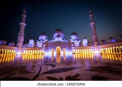 Abu Dhabi, UAE - July 1 2019 : Amazing Grand Mosque. Sheikh Zayed Grand Mosque at sunset time, illuminated and crescent visible between two minarets. People visit the mosque for praying. Holy concept.