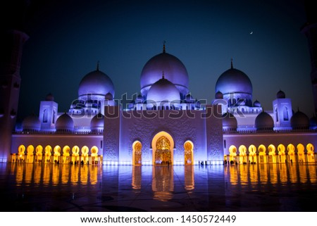 Abu Dhabi, UAE - July 1 2019 : Sheikh Zayed Grand Mosque in Abu Dhabi, illuminated at night and crescent visible. People visiting the mosque for praying.Domes and crescent visible.   Mosque concept.