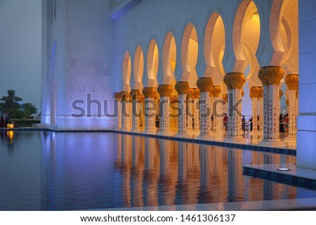 Abu Dhabi, UAE - July 1 2019 : Sheikh Zayed Grand Mosque's one side view. The columns are illuminated with yellow lights and very nice reflection on the pool next to the columns. Holy place.