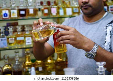 Abu Dhabi, UAE - July 24, 2018:  A skillful perfume vendor mixes and blends various fragrances to make Arabic perfume in Abu Dhabi