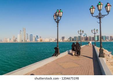 ABU DHABI, UAE - MARCH 7, 2017: People watch the skyline of Abu Dhabi from the Marina Breakwater, United Arab Emirates