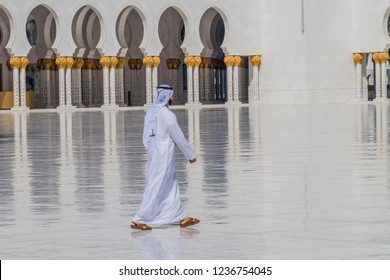 ABU DHABI, UAE - MARCH 9, 2017: Local man walks at the courtyard of Sheikh Zayed Grand Mosque in Abu Dhabi