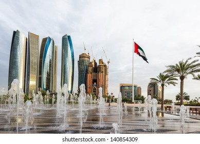 ABU DHABI, UAE - MAY 1: Etihad Towers with UAE flag on May 1, 2013 in Abu Dhabi, UAE. Etihad Towers is the name of a complex of buildings with five towers in Abu Dhabi, the capital city of UAE.