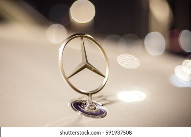 ABU DHABI, UAE - NOV 26, 2016: Mercedes Benz company logo on a car illuminated at night