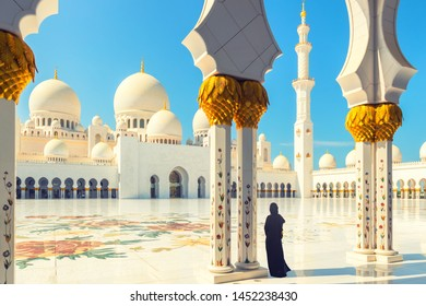 Abu Dhabi, UAE – November 11, 2018: Woman in traditional dress inside Sheikh Zayed Mosque – tourist wearing black abaya visiting famous arabian religious temple in Abu Dhabi, United Arab Emirates