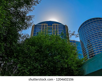 Abu Dhabi, UAE - October 7, 2018: Low angle of a the sun behind a tower in Abu Dhabi city - Al Wahda Mall