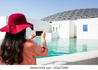 ABU DHABI, UNITED ARAB EMIRATES - JANUARY 26, 2018: Female tourist taking picture of Louvre Abu Dhabi building. Louvre is a new museum in United Arab Emirates opened on November 8th 2017