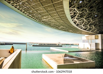 ABU DHABI, UNITED ARAB EMIRATES - APRIL 2, 2018: Female tourist looking at Louvre Abu Dhabi building