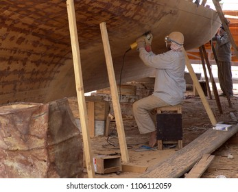 Abu Dhabi, United Arab Emirates - April 11, 2004: Worker at a shipbuilding yard polishes a traditional wooden Arabian dhow with a machine